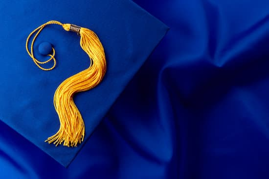 Blue mortarboard and yellow tassel shot on blue graduation gown, space for copy